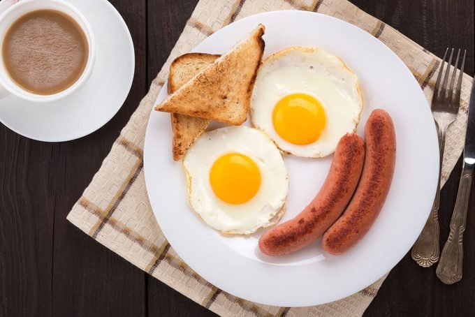 Delicious breakfast. Served on a wooden table with toast, eggs, sausage, wafers, coffee, orange juice, jam, knife, fork. Horizontal image. Top view. View from above