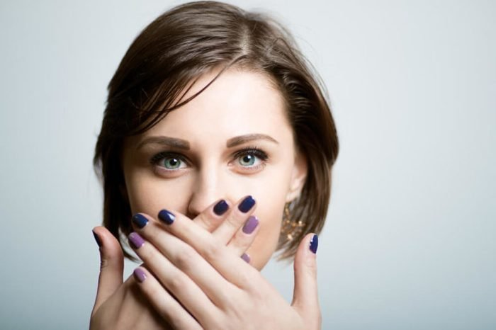 Pretty slender girl covers her mouth with her hands