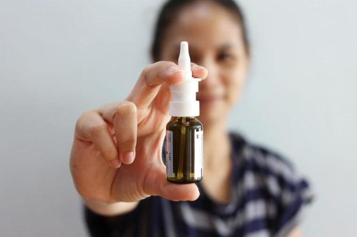 Female holding a nasal spray bottle.