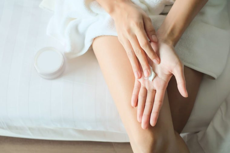Asian woman sitting on a bed and applying cream on her hand.
