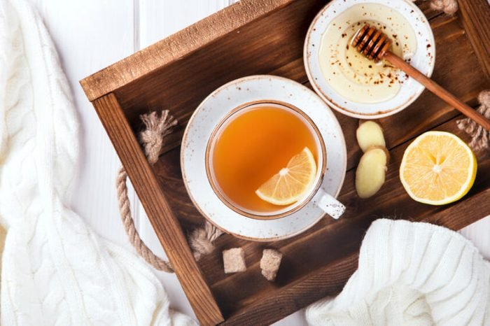 Cup of Ginger Tea with Lemon and Honey on a tray served in bed.