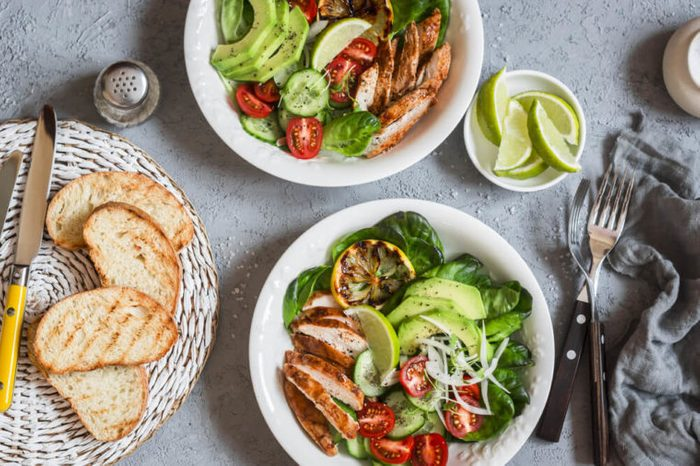 Grilled chicken and fresh vegetable salad on a light background, top view.