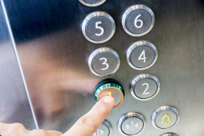 finger pressing elevator button
