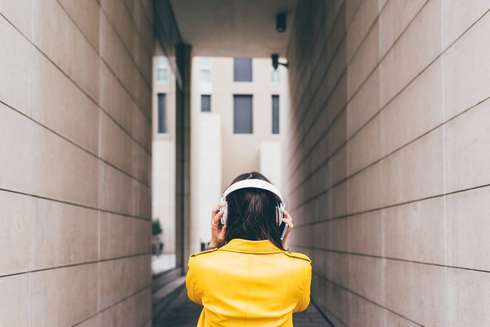 From behind view of young caucasian brown hair woman listening music with headphones - music, technology, relax concept