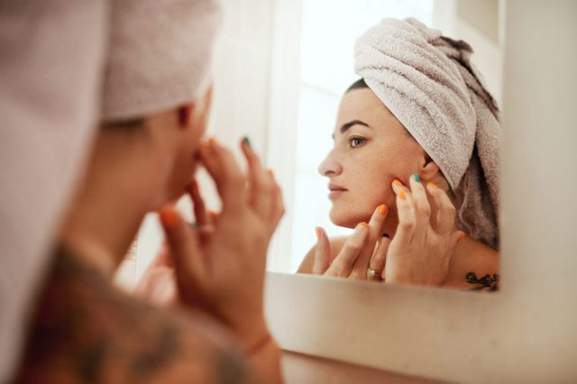woman inspecting her skin in mirror after taking a shower
