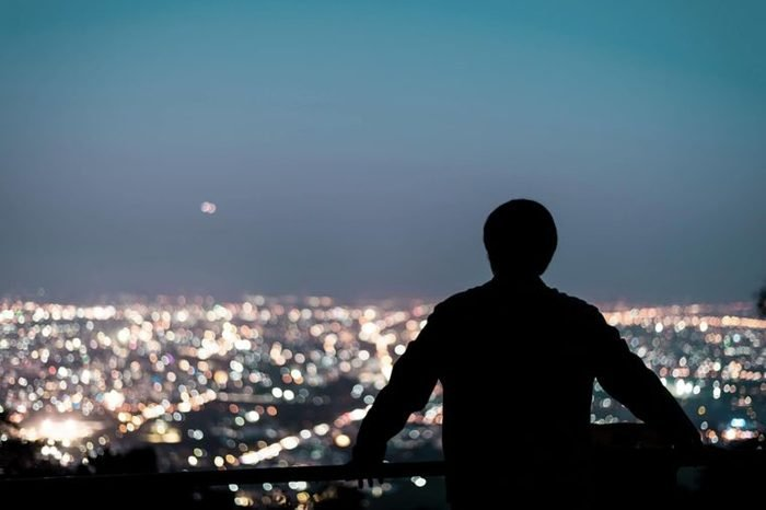 man on a balcony at night staring at city skyline
