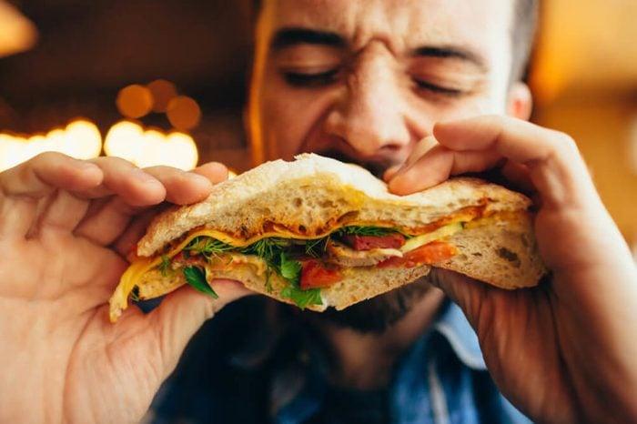 Man in a restaurant eating a flatbread sandwich