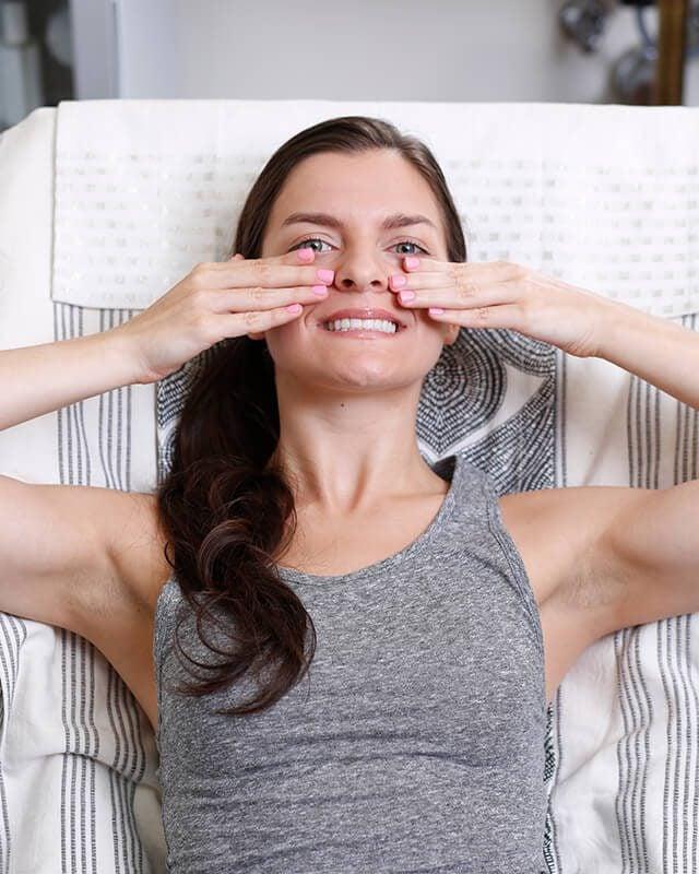 Woman rubbing her cheeks to improve her skin.