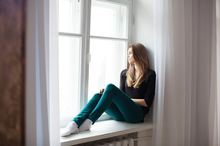 Sad woman in green pants sitting on a window ledge.