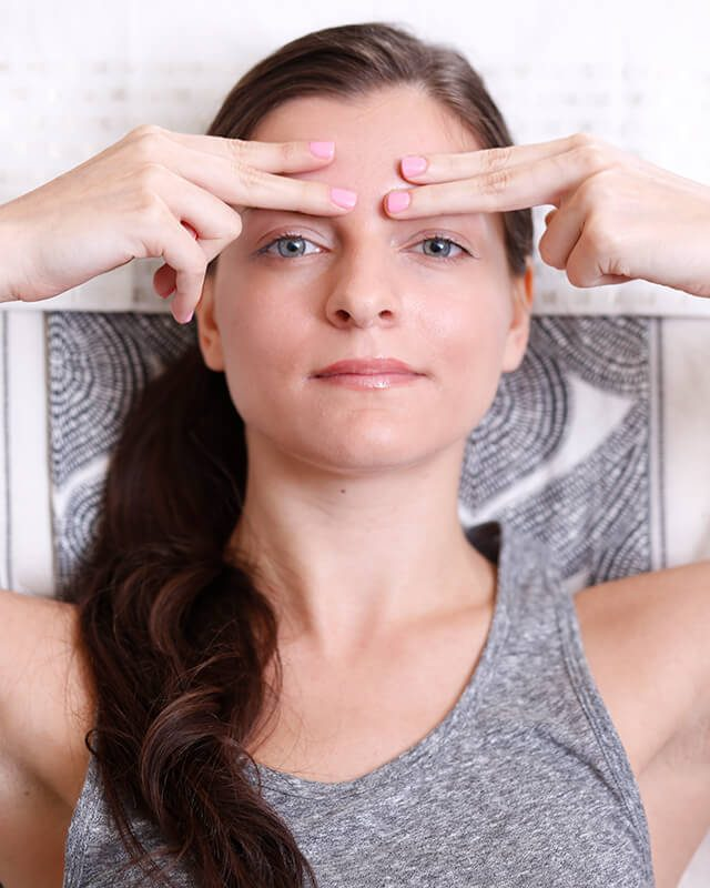 Woman doing facial exercises to make her skin look younger.