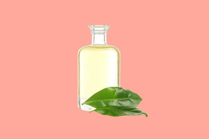 bottle of tea tree oil with leaves
