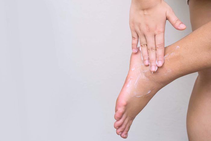 Woman-applying-cream-on-foot