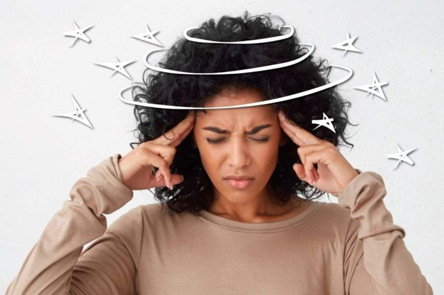 black woman pressing her fingers against her temples