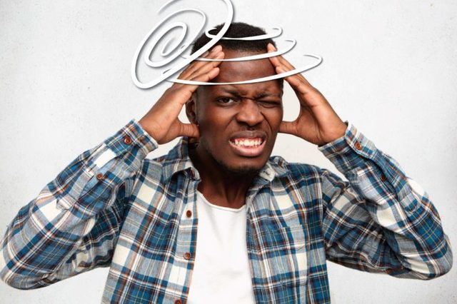 black man wincing in pain and holding his head