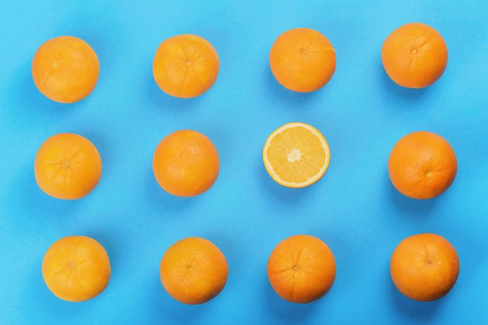 background of orange pattern, one oranges cut in half, top view, blue background, studio shot