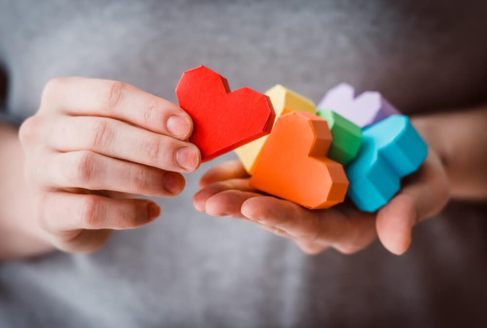 Hands holding rainbow paper hearts
