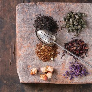 Variety of black, green, rooibos, herbal dry tea leaves and rose buds with vintage strainer on terracotta board over old dark wooden background. Top view with copy space