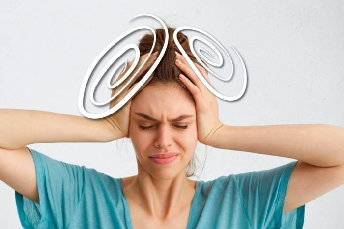 woman squeezing her head with her hands