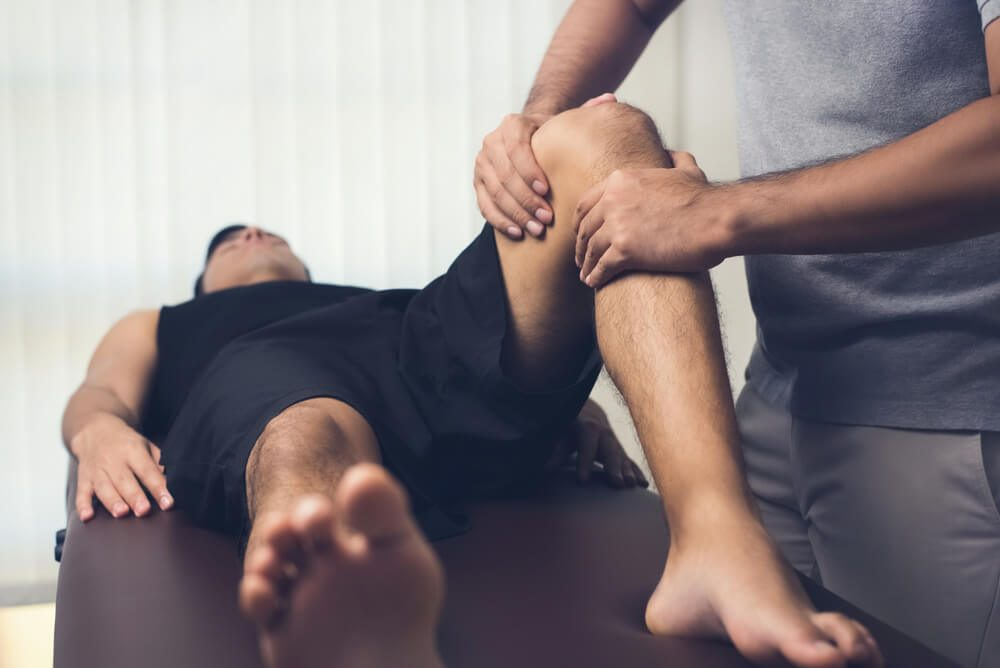 therapist massaging knee of male patient