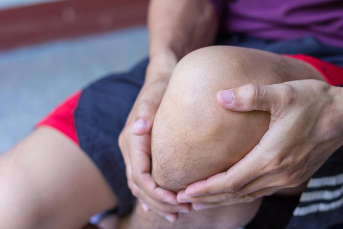 man with hands on his knee, knee pain