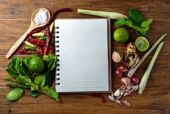 empty journal surrounded by garlic, spices and herbs