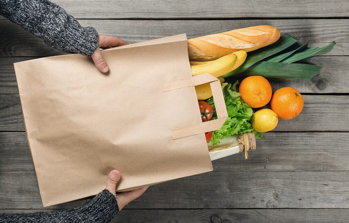 Man's hands holding paper bag of groceries, top view