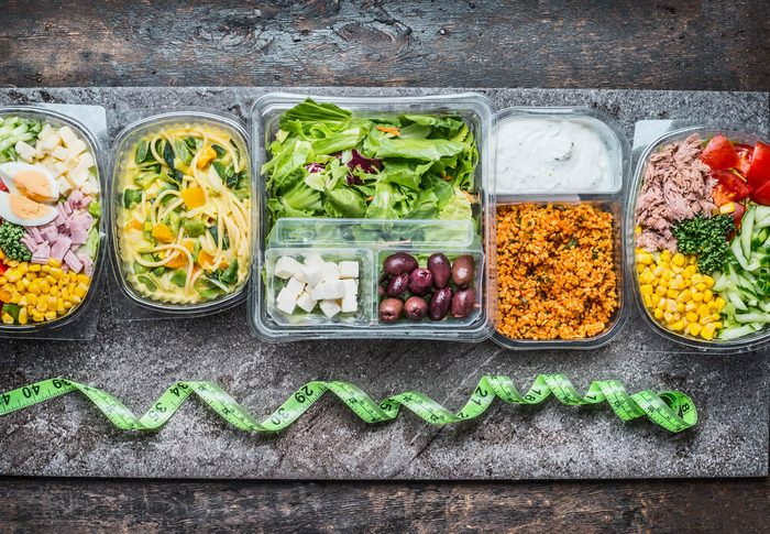 healthy containers of salads and other foods and green measuring tape