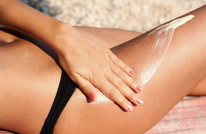 woman applying sunscreen on leg
