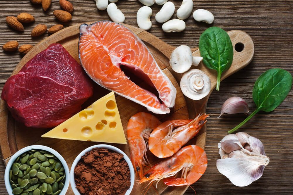 Foods High in Zinc as salmon, seafood-shrimps, beef, yellow cheese, spinach, mushrooms, cocoa, pumpkin seeds, garlic, bean and almonds. Top view