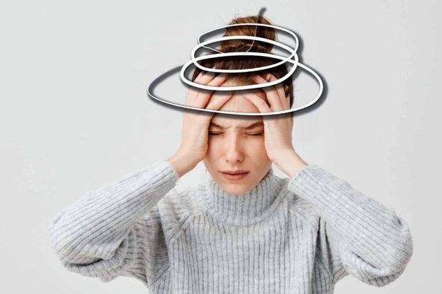 woman holding her head, eyes shut
