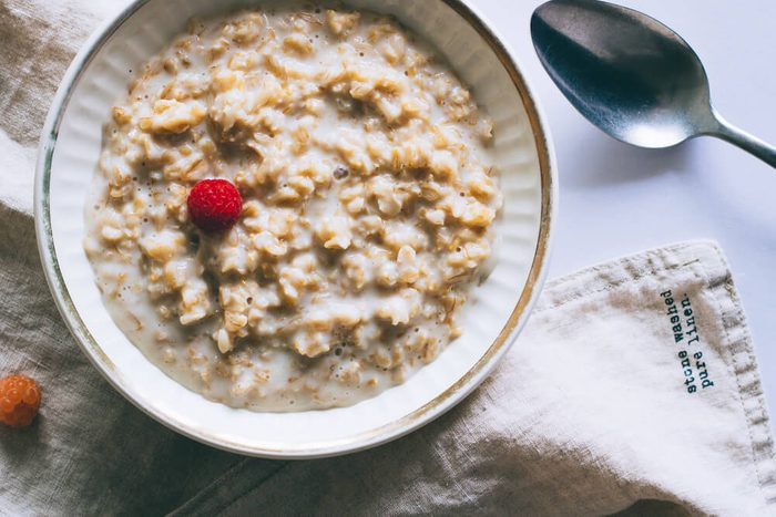 Morning breakfast, oatmeal in milk with raspberries on a white background, top view
