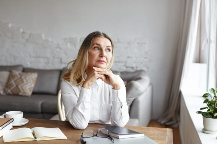 Middle-aged woman sitting at a desk and gazing out the window, deep in thought