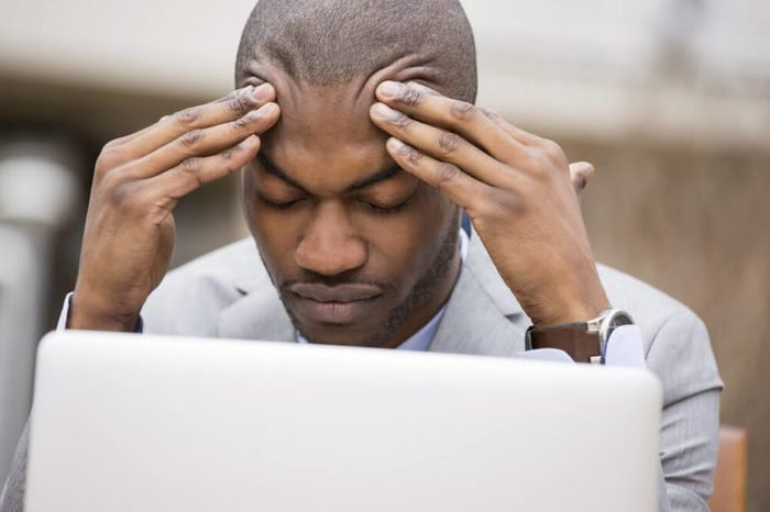 stressed young businessman working on laptop computer holding head with hands looking down.