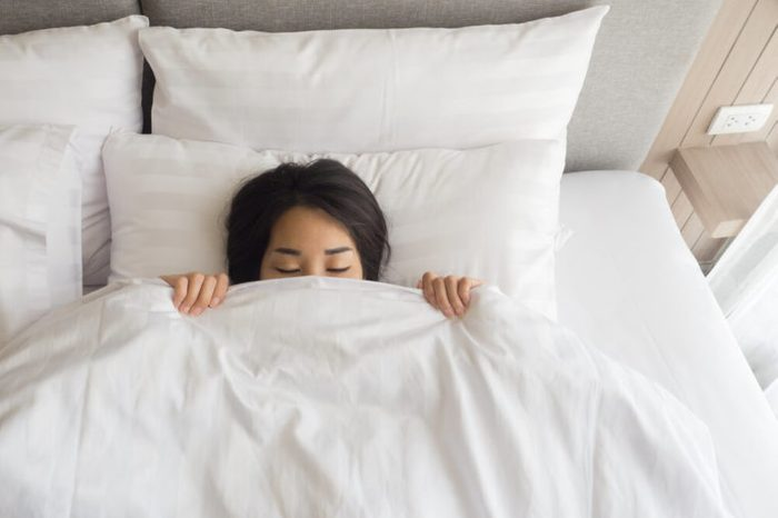 Close-up of young woman sleeping under white blanket