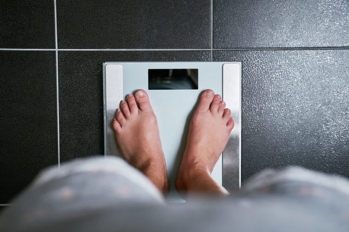 Female bare feet stepping on a weight scale