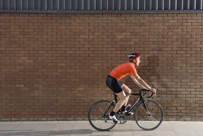 Full length side view of a young man cycling past brick wall