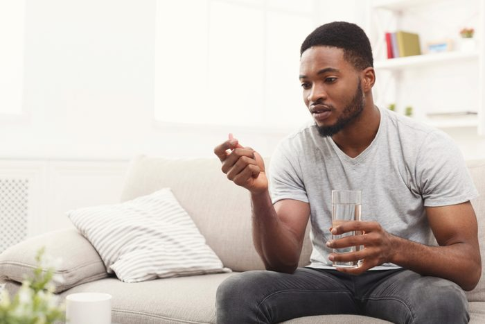 Serious african-american man ready to take a pill while sitting on a couch at home, copy space