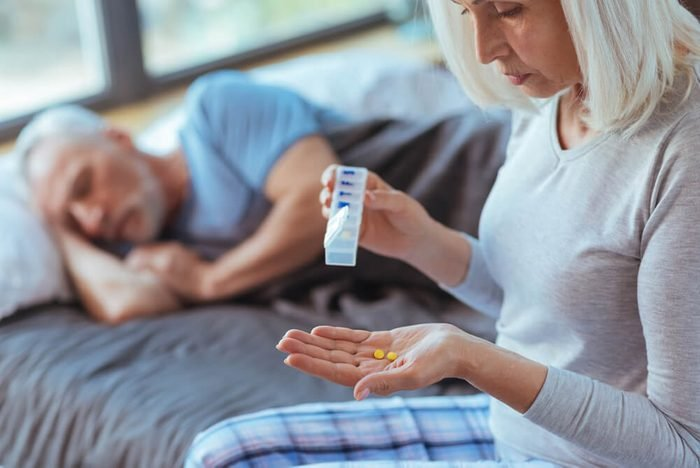 Cheerless aged woman holding pills for her husband