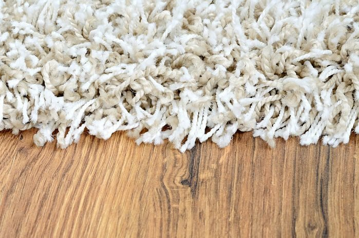 Close-up detail of white shaggy carpet on brown wooden floor