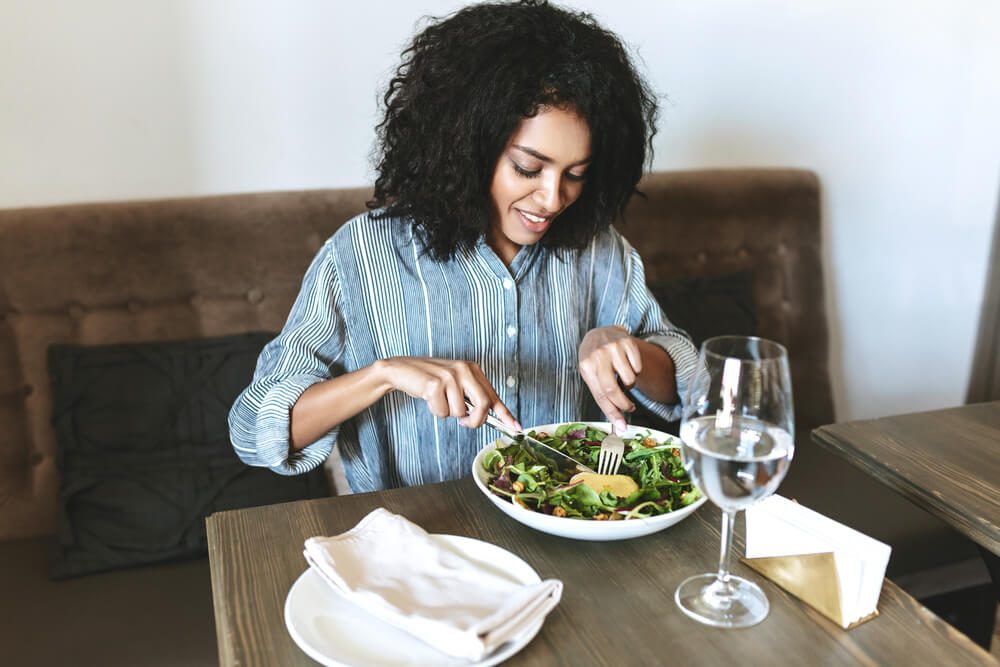 Young womaneating salad in restaurant. Beautiful girl with dark curly hair sitting at cafe and eating salad. Portrait of smiling lady that have lunch in restaurant