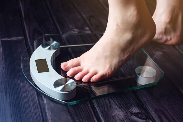 Female feet standing on electronic scales for weight control on wooden background