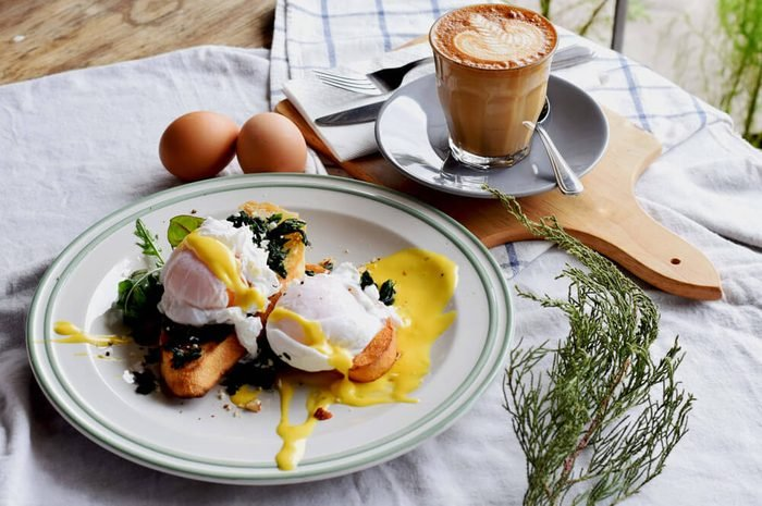Breakfast Set, Egg benedict in white dish and a great coffee. Latte art. Wood background.