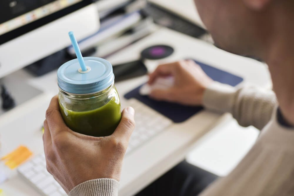 closeup of a young man drinking a green smoothie served in a glass jar at the office