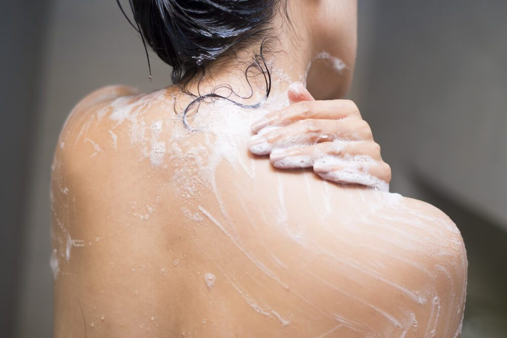young woman washing her body with shower gel, healthcare