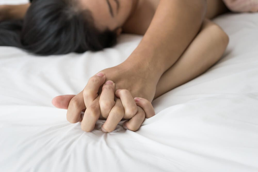 Young couple making love in bed focus on hand