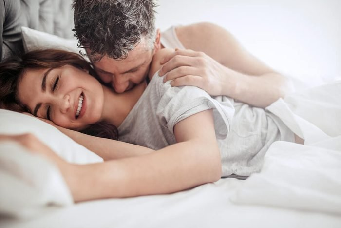 Beautiful passionate couple waking up in bed. Man kissing on neck of woman, both lying on bed.