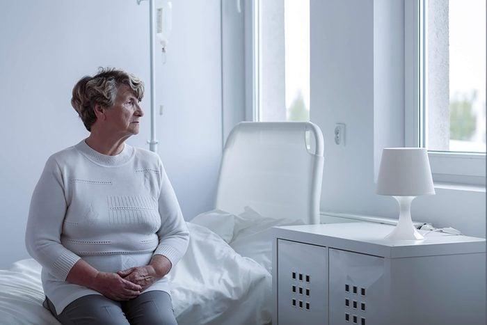 Elderly woman sitting on bed