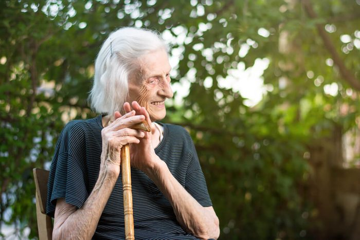 Cheerful senior woman sitting with a walking cane