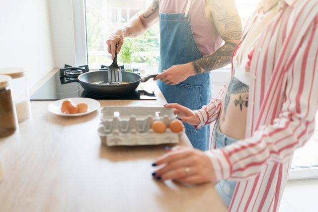 couple making breakfast together in kitchen at home