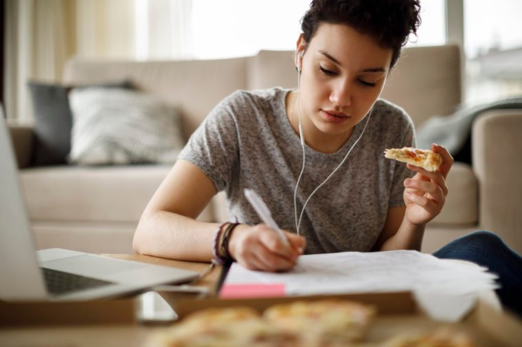 female student studying and eating pizza